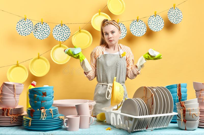 Puzzled surprised woman wearing apron shrugging her shoulders in perplexity stock photo