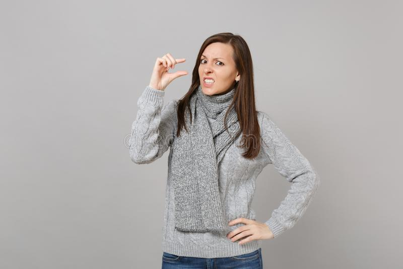 Puzzled woman in gray sweater scarf gesturing demonstrating size with copy space on grey background. Healthy. Fashion lifestyle people sincere emotions cold royalty free stock image