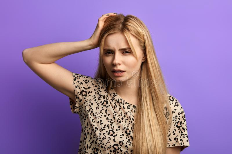 Young puzzled woman, scratching her head, thinking, daydreaming stock images