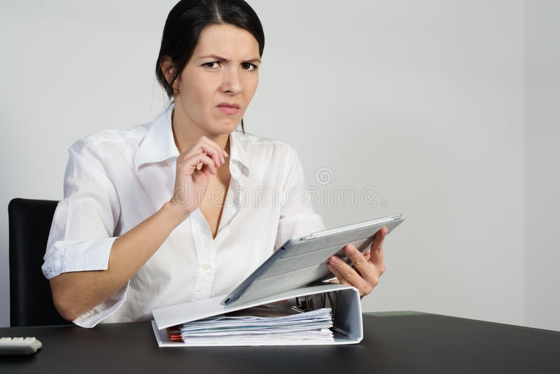 Puzzled woman thinking hard. And grimacing as she tries to find an answer to a problem posed on her handheld tablet computer royalty free stock image