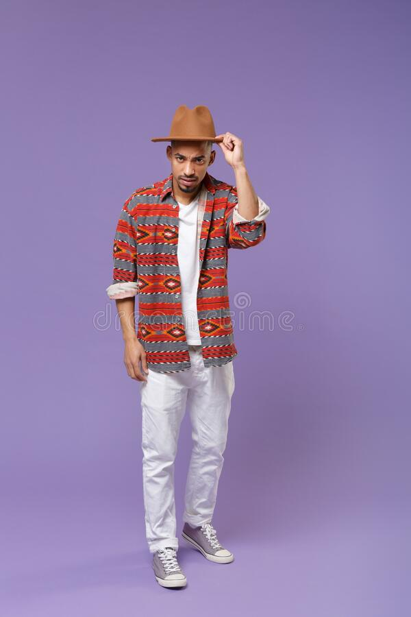 Puzzled young african american guy in casual colorful shirt hat posing isolated on violet background studio portrait stock photography