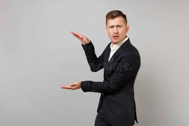 Puzzled young business man in classic black suit gesturing demonstrating size with vertical copy space isolated on grey. Wall background. Achievement career royalty free stock photography