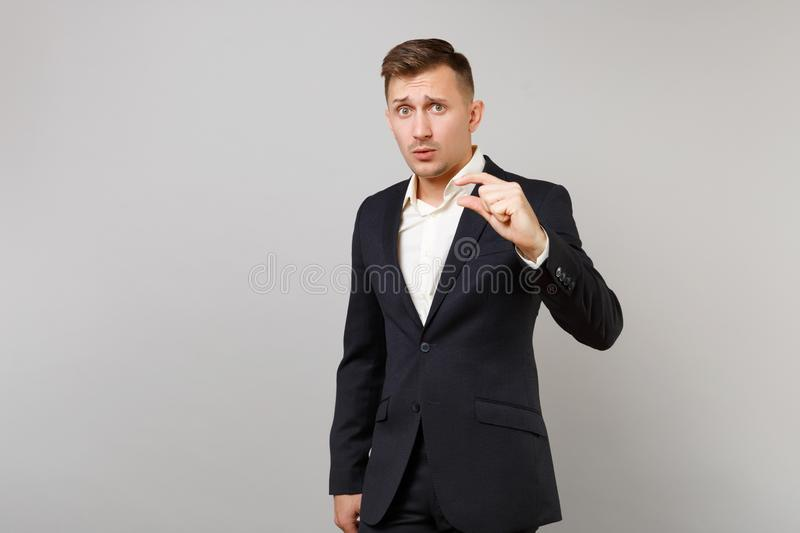 Puzzled young business man in classic black suit, shirt gesturing demonstrating size with copy space isolated on grey. Wall background. Achievement career royalty free stock images