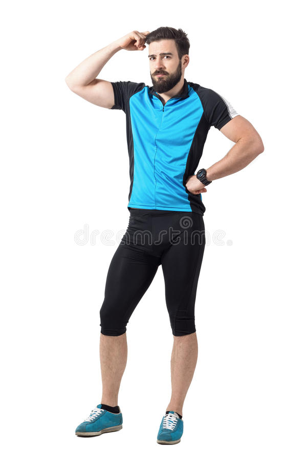Puzzled young cyclist in sports clothes scratching head looking at camera. stock images