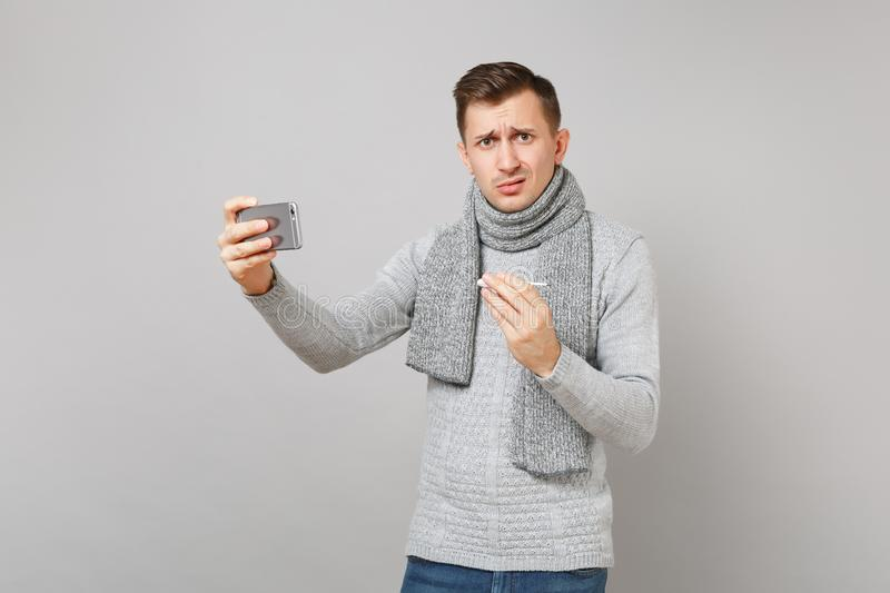 Puzzled young man in gray sweater, scarf holding thermometer, doing selfie shot on mobile phone, making video call. On grey background. Health, ill sick disease stock photos