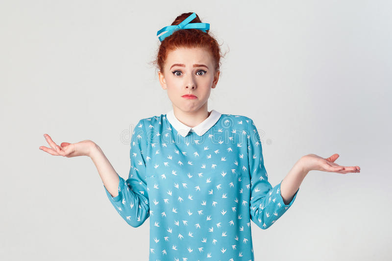 Puzzled young redhead girl with arms out, shrugging her shoulders, saying: who cares, so what, I don`t know. royalty free stock photo