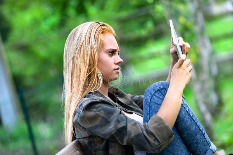 Puzzled young woman staring at a tablet computer. Puzzled young woman staring at a handheld tablet computer twisting it in her hands as she relaxes on a bench stock photo
