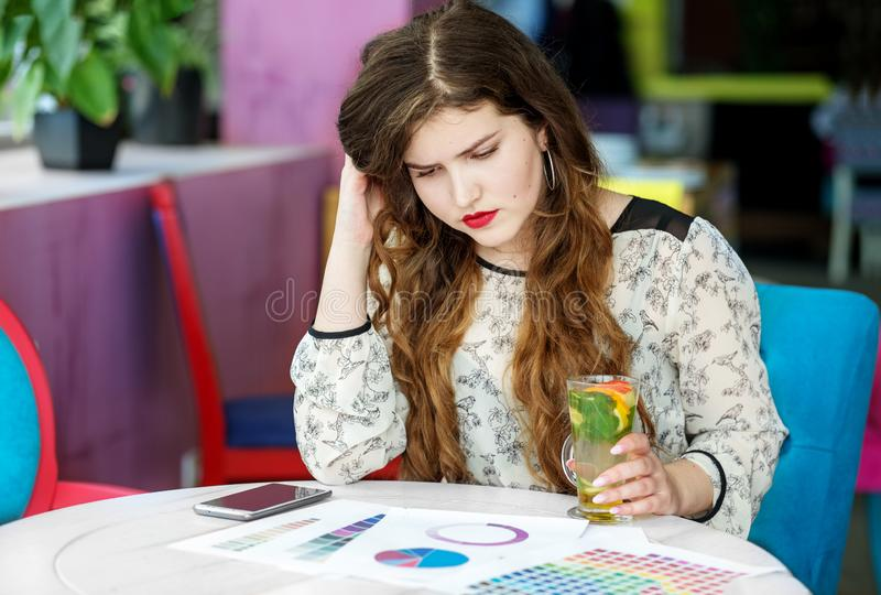 Puzzled young woman thinks about the project. Citrus tea with mint. The concept of work, business, education, freelance, lifestyle.  stock images