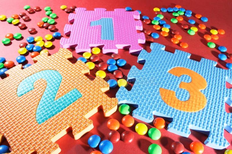 Puzzles de numéro et sucettes de chocolat photo stock