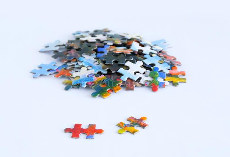 Puzzles multicolores de carton sur le fond blanc Plan rapproché photos stock