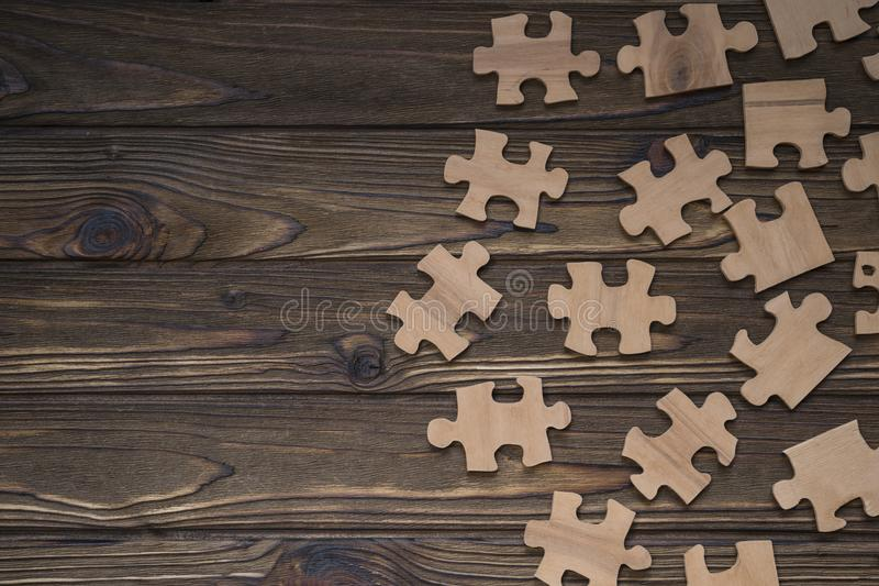 Puzzles on a wooden background. Figures from natural wood. royalty free stock image