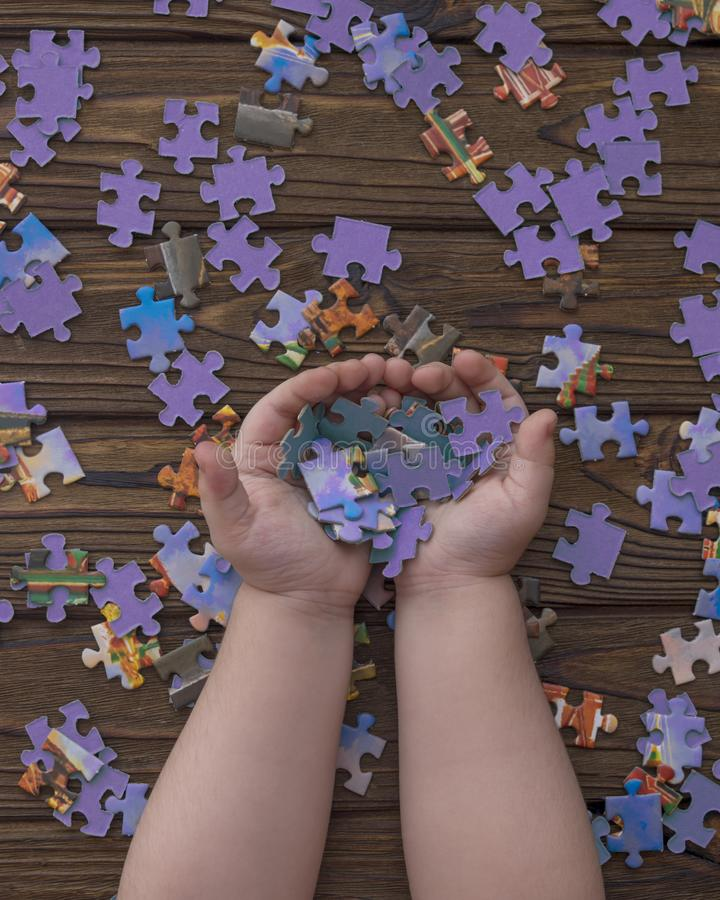 Pieces of puzzles in the hands of a child. Puzzles on a wooden background. pieces of puzzles in the hands of a child. logical game. preschool education royalty free stock photos