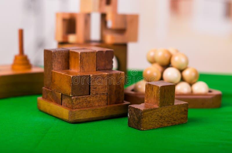 Puzzlespiel der Holzklotzgehirnharten nuss auf grüner Tabelle in einem unscharfen Hintergrund stockfoto