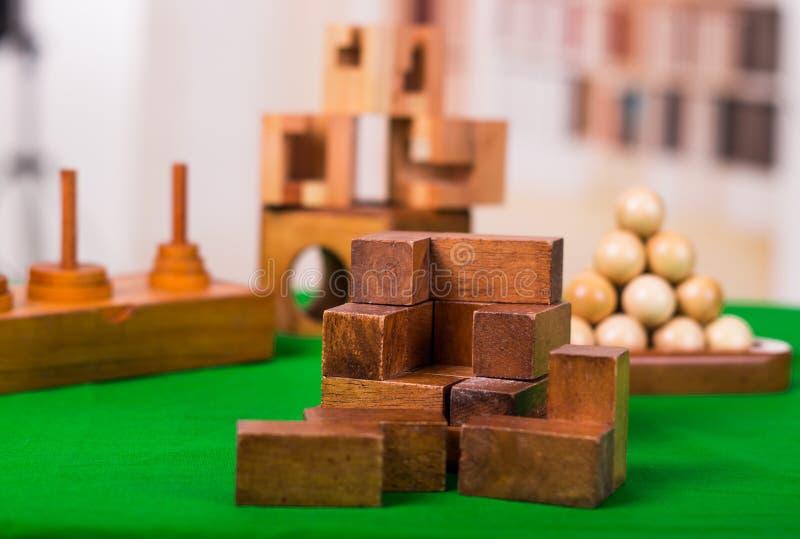 Puzzlespiel der Holzklotzgehirnharten nuss auf grüner Tabelle in einem unscharfen Hintergrund lizenzfreie stockfotografie