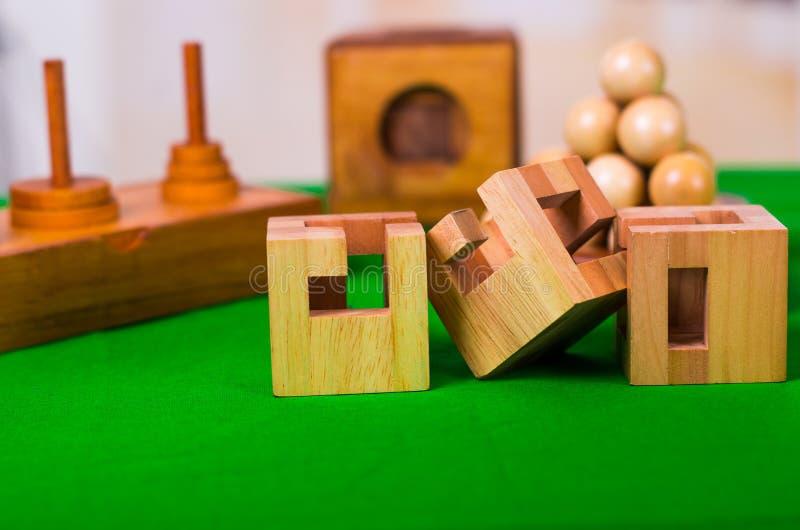 Puzzlespiel der Holzklotzgehirnharten nuss auf grüner Tabelle in einem unscharfen Hintergrund lizenzfreie stockfotos