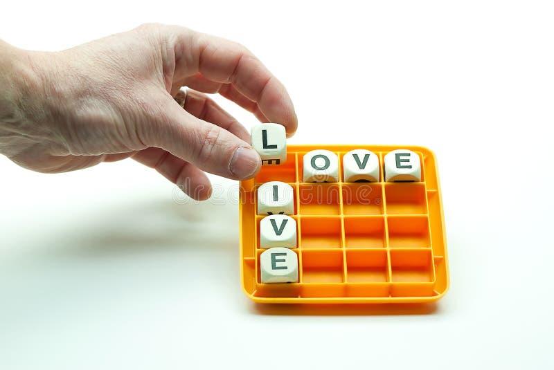 Puzzlespiel lösend, um die Wörter zu bilden, leben Sie und lieben Sie stockbilder