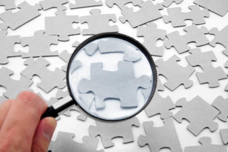 Puzzlespiel und Vergrößerungsglas stockfotografie