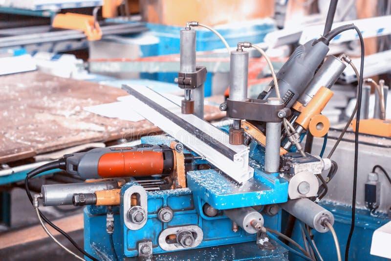 PVC窗口的生产,钻孔的在框架pvc,钻子工具一个机器 免版税库存照片