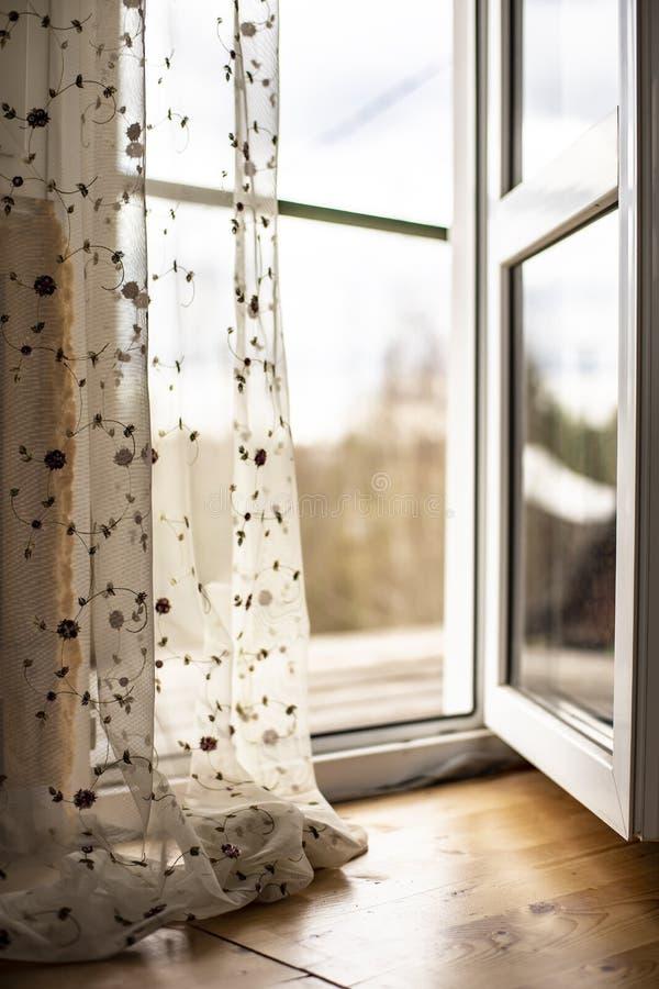 PVC för öppen dörr med en balkong i huset, bredvid hängande tul royaltyfria bilder