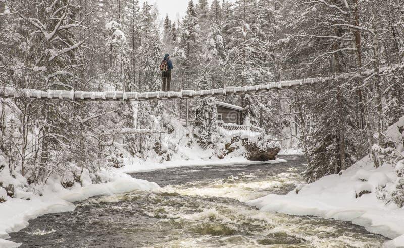 Pwerson auf einer hängenden Brücke in einer Winterlandschaft stockbilder