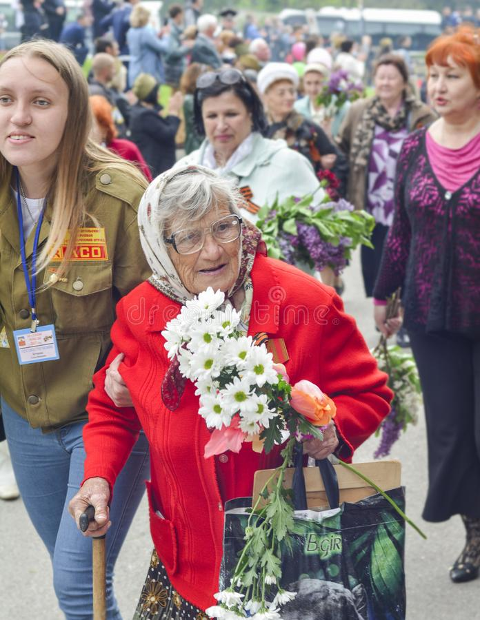 PYATIGORSK, RUSSIA - MAY 09, 2017: War veteran woman with flowers on the Victory Day celebration. Russian babushka royalty free stock photo