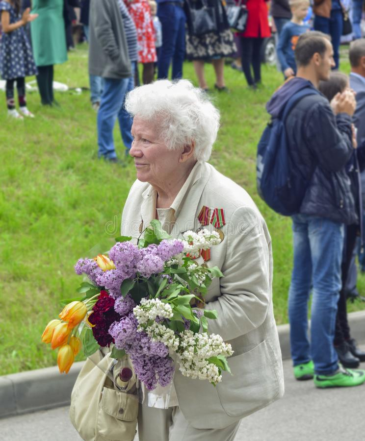 PYATIGORSK, RUSSIA - MAY 09, 2017: War veteran woman with flowers on the Victory Day celebration. Russian babushka royalty free stock photos