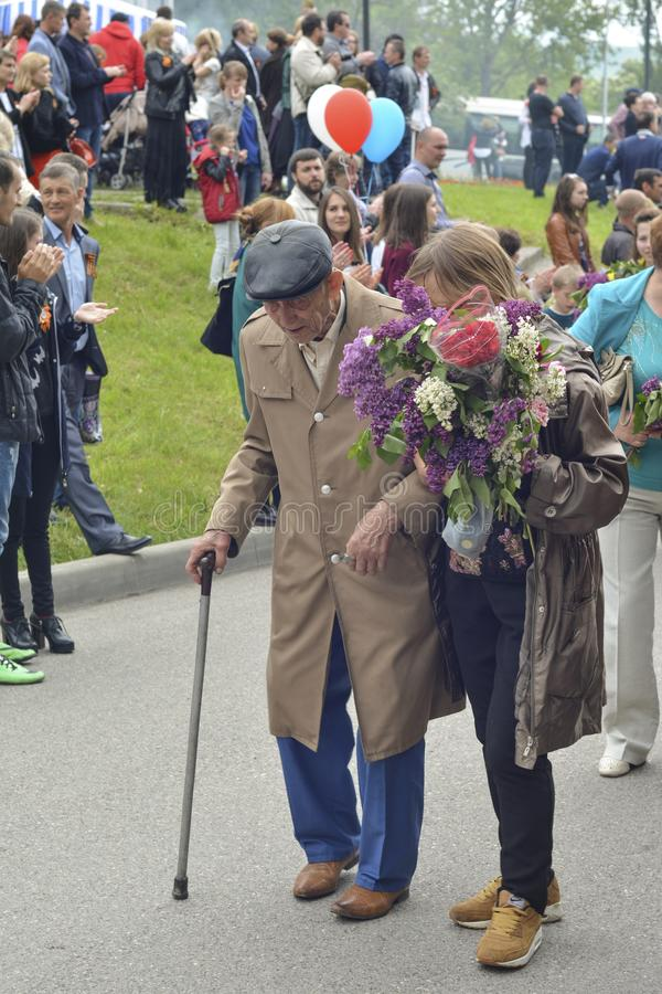 PYATIGORSK, RUSSIA - MAY 09, 2017: Young carer and elderly man with a walking stick on Victory Day. On a parade of 9 may royalty free stock image