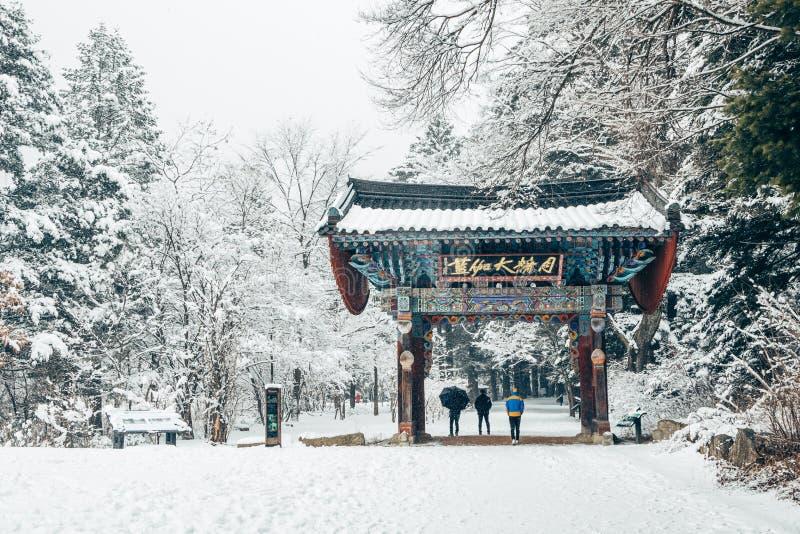Pyeongchang, Corée - 18 février 2015 : Temple asiatique Odaesan Woljeongsa avec la route d'arbre de sapin de l'hiver neigeux photos stock
