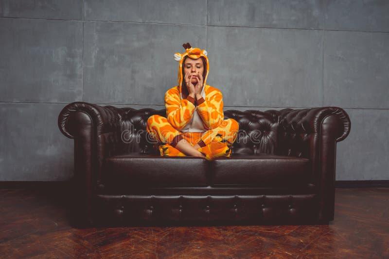 Pyjama's voor Halloween in de vorm van een giraf Emotioneel portret van een meisje op een bankachtergrond Gekke en grappige mens  stock foto