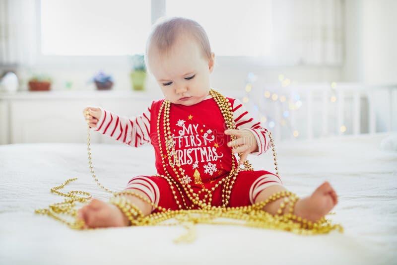 Pyjamas счастливого маленького ребенка нося играя с украшениями дерева Нового Года стоковое фото rf