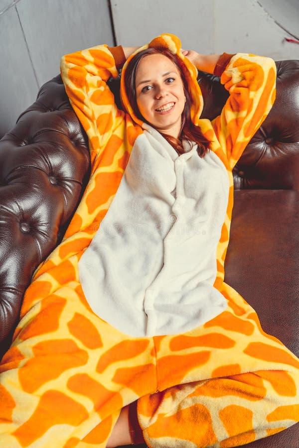 Pyjamas für Halloween in Form einer Giraffe Emotionales Porträt eines Mädchens auf einem Sofahintergrund Verrückter und lustiger  stockfoto