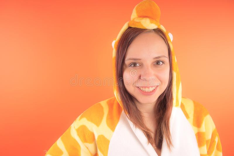 Pyjamas i form av en giraff emotionell stående av en flicka på en orange bakgrund galen och rolig kvinna i en dräkt _ royaltyfri foto
