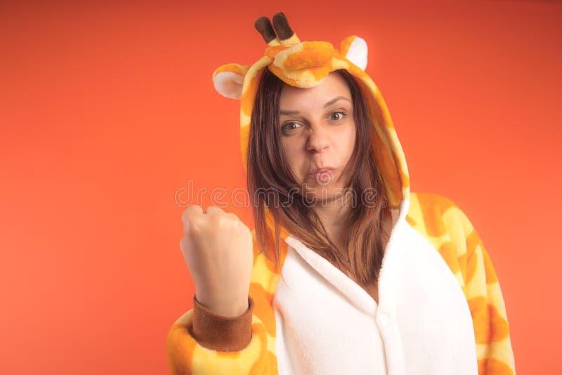 Pyjamas i form av en giraff emotionell stående av en flicka på en orange bakgrund galen och rolig kvinna i en dräkt _ royaltyfri bild
