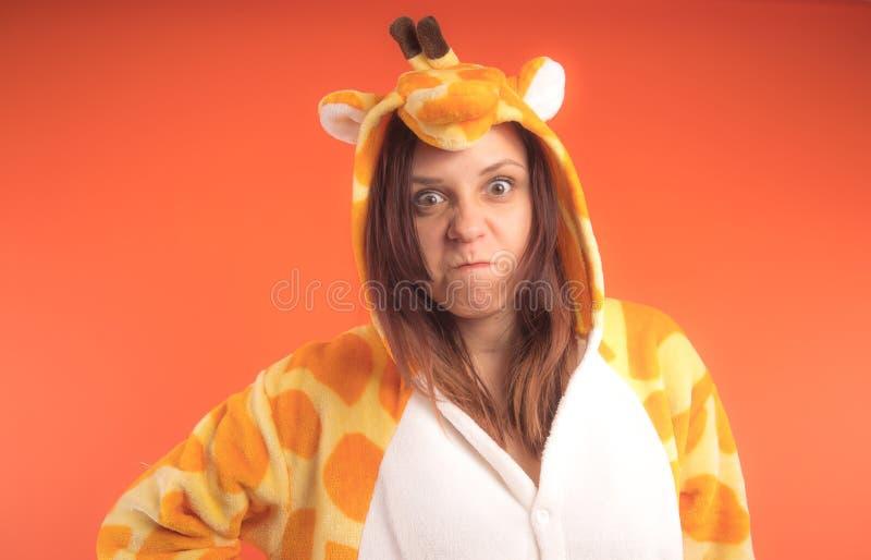 Pyjamas i form av en giraff emotionell stående av en flicka på en orange bakgrund galen och rolig kvinna i en dräkt _ arkivbilder
