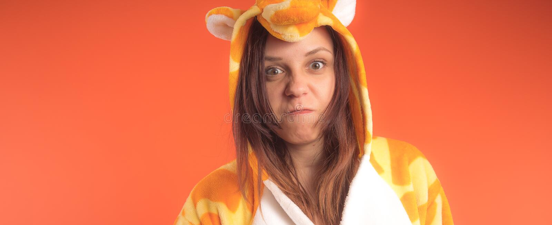 Pyjamas i form av en giraff emotionell stående av en flicka på en orange bakgrund galen och rolig kvinna i en dräkt _ fotografering för bildbyråer