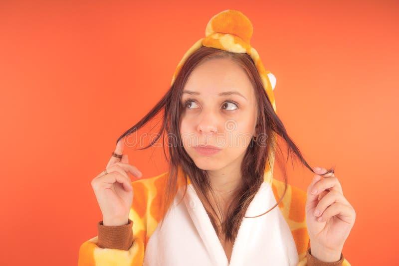 Pyjamas i form av en giraff emotionell stående av en flicka på en orange bakgrund galen och rolig kvinna i en dräkt _ arkivfoton