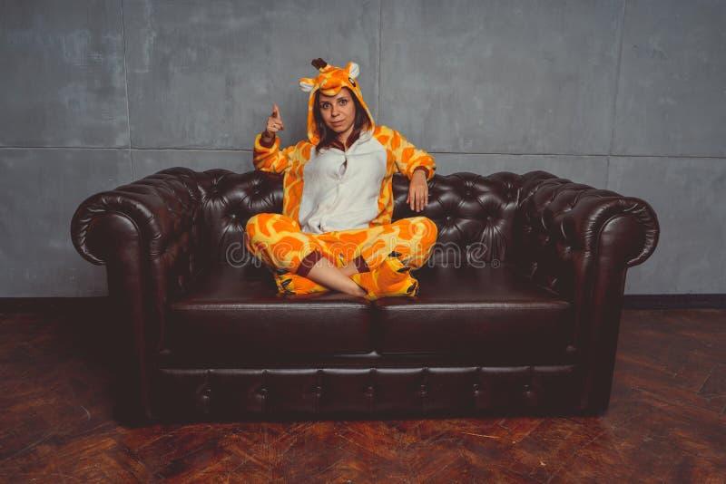 Pyjamas pour Halloween sous forme de girafe Portrait émotif d'une fille sur un fond de sofa Homme fou et drôle dans un costume images libres de droits