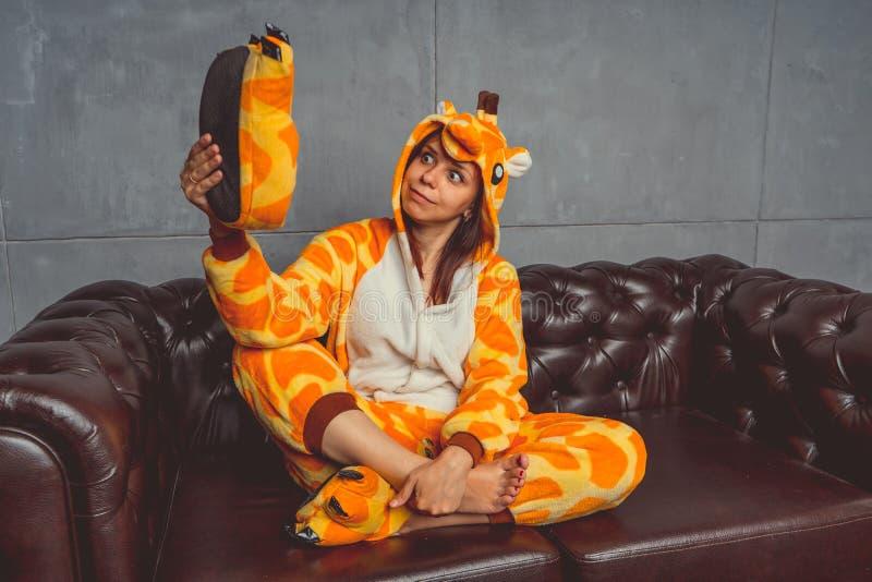 Pyjamas pour Halloween sous forme de girafe Portrait émotif d'une fille sur un fond de sofa Homme fou et drôle dans un costume image libre de droits