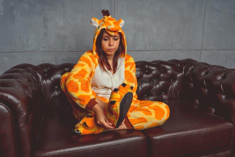 Pyjamas pour Halloween sous forme de girafe Portrait émotif d'une fille sur un fond de sofa Homme fou et drôle dans un costume images stock
