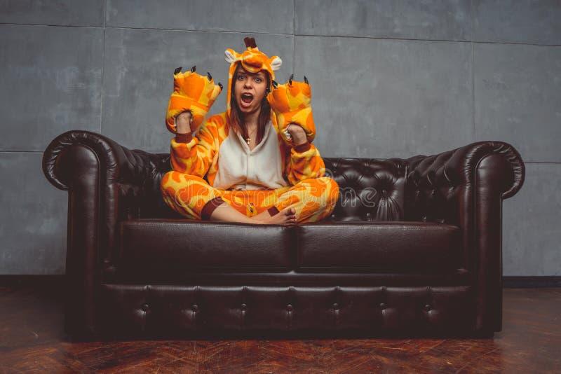 Pyjamas pour Halloween sous forme de girafe Portrait émotif d'une fille sur un fond de sofa Homme fou et drôle dans un costume photo libre de droits