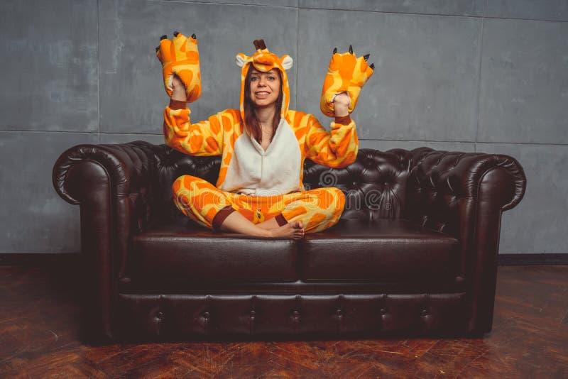 Pyjamas pour Halloween sous forme de girafe Portrait émotif d'une fille sur un fond de sofa Homme fou et drôle dans un costume photographie stock libre de droits