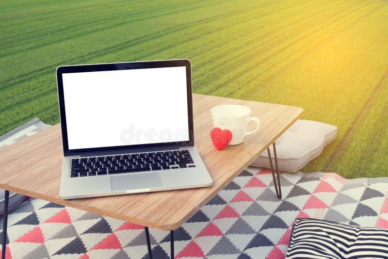 Pykniczny stół z pustym ekranem na laptopie i białej filiżance, r fotografia royalty free