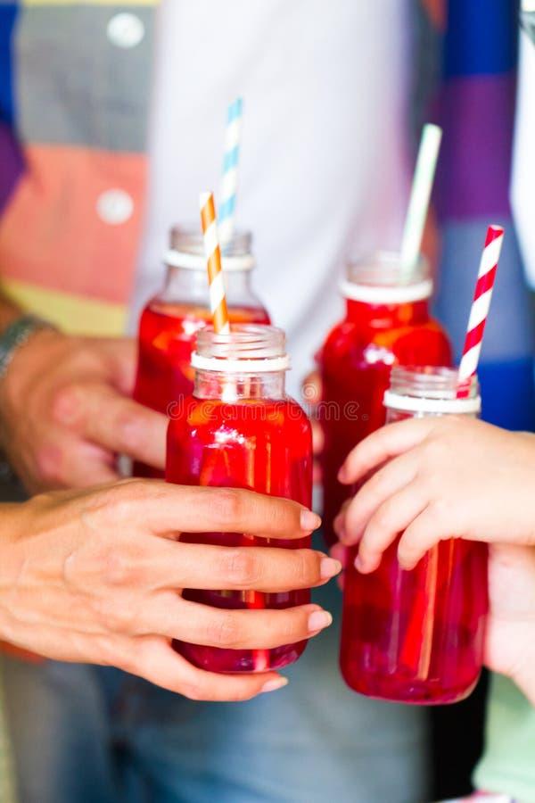 Pykniczny temat: szczęśliwi młodzi rodzinni mienie napoje, grzanki butelka w obrazy stock