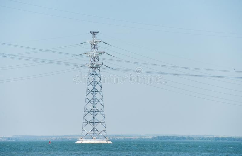 Pylône à haute tension des lignes électriques sur la rivière photos stock
