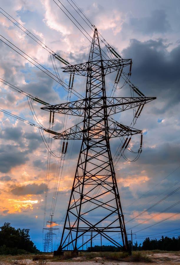 Pylône de transmission de l'électricité silhouetté contre le ciel bleu au crépuscule photos libres de droits