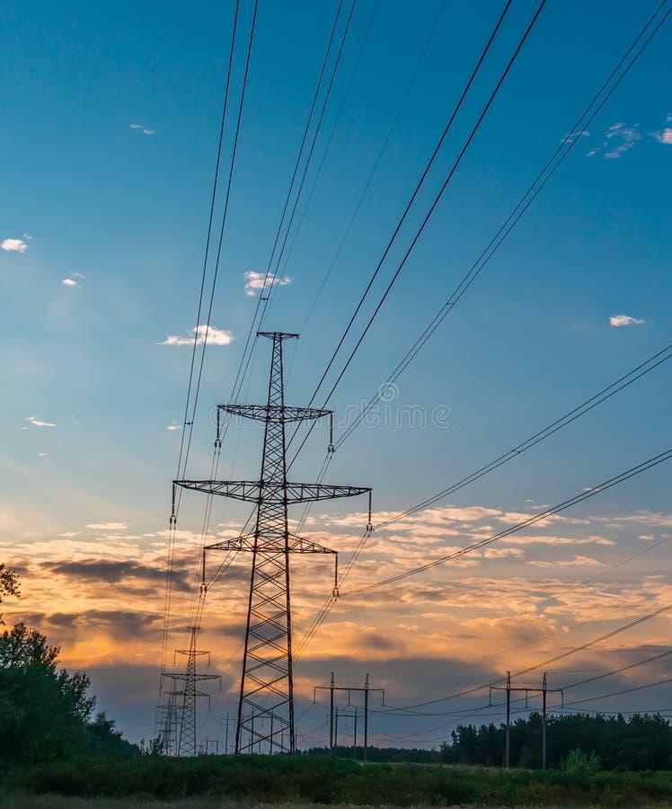 Pylône de transmission de l'électricité silhouetté contre le ciel bleu au crépuscule images stock