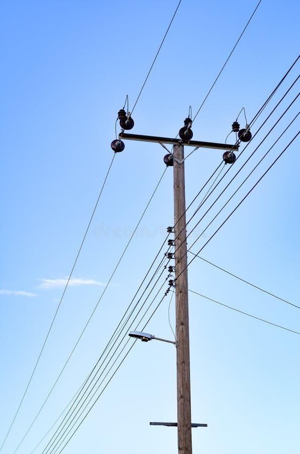 Pylône en bois de l'électricité contre le ciel bleu clair images libres de droits