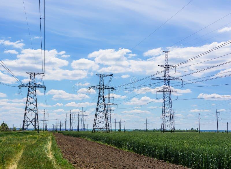 Pylônes de l'électricité entrant dans la distance au-dessus de la campagne d'été images stock
