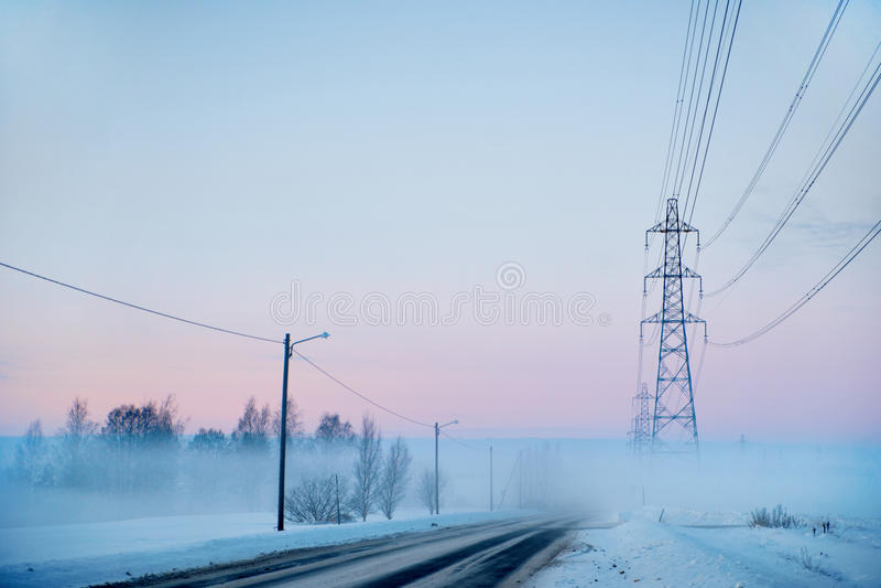 Pylônes de route et d'evlectricity de campagne en hiver images libres de droits