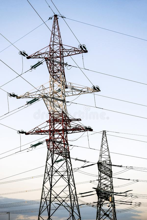 Pylônes en métal des lignes électriques à haute tension contre le ciel égalisant image stock